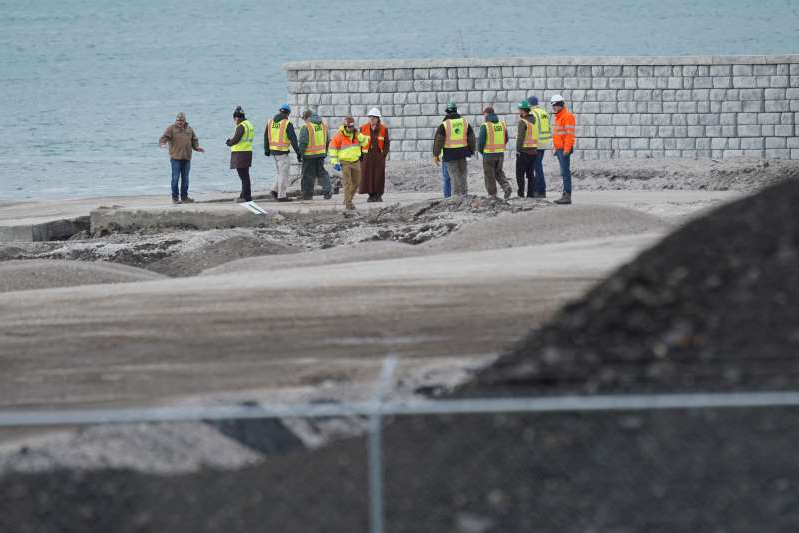 a group of people walking on a beach: People survey the scene of a Detroit property contaminated with uranium and other dangerous chemicals that partially collapsed into the Detroit River on Friday, Dec. 6, 2019.