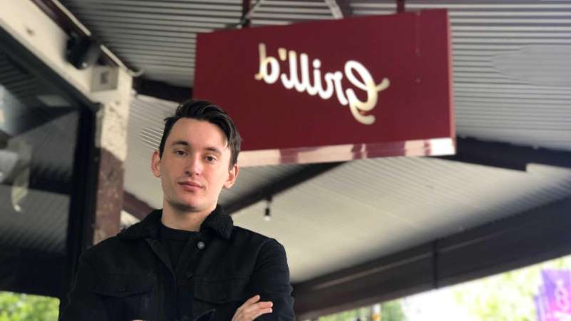 a man standing in front of a window: Grill'd worker Patrick Stephenson said he had struggled to pay rent while working for the burger chain. (ABC News: Jedda Costa)
