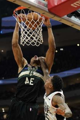 a person holding a basketball: Milwaukee Bucks' Giannis Antetokounmpo dunks over Los Angeles Clippers' Lou Williams during the second half of an NBA basketball game Friday, Dec. 6, 2019, in Milwaukee. (AP Photo/Morry Gash)