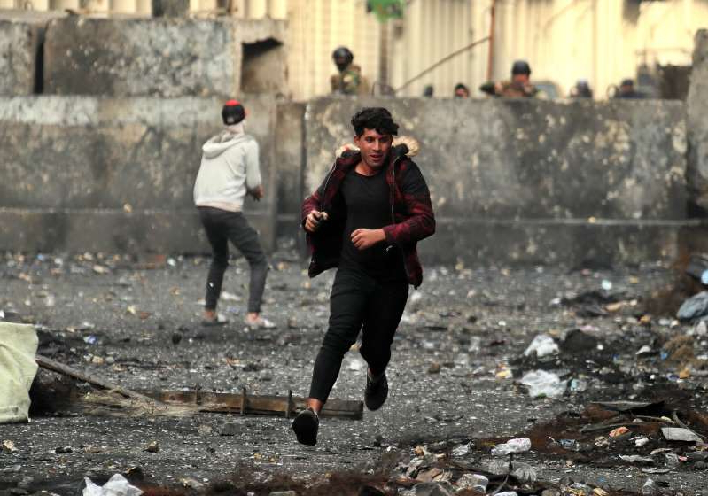 Anti-government protesters throw stones while security forces close Rasheed Street during clashes in Baghdad, Iraq, Friday, Dec. 6, 2019. (AP Photo/Hadi Mizban)