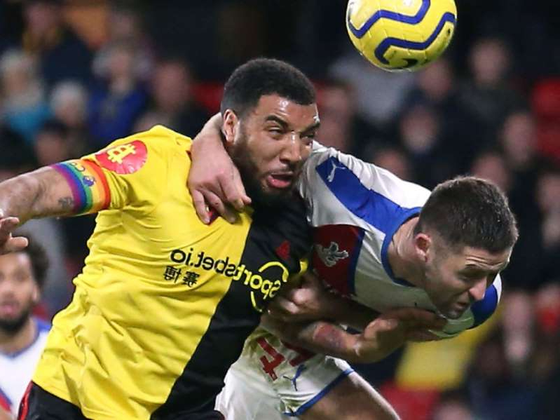 Troy Deeney holding a football ball: Troy Deeney is held by Gary Cahill as they both challenge for the ball