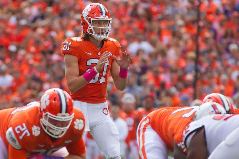 a baseball player holding a bat on a field: Clemson quarterback Trevor Lawrence prepares to take a snap during his team's game against North Carolina State in 2018.
