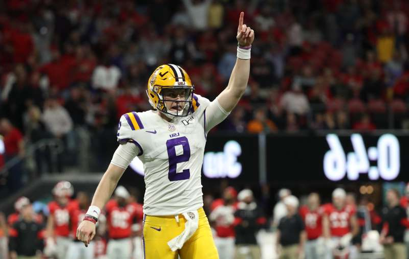 a crowd of people watching a baseball game: LSU quarterback Joe Burrow celebrates a touchdown in the SEC title game.