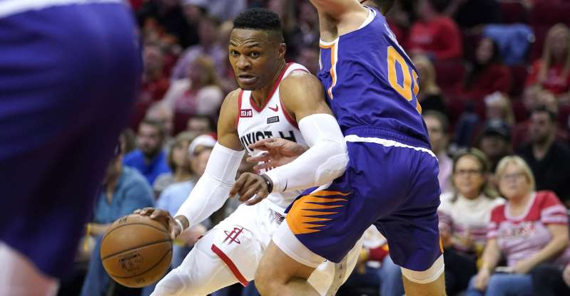a crowd of people watching a football ball: Houston Rockets' Russell Westbrook, right, drives toward the basket as Phoenix Suns' Ty Jerome (10) defends during the first half of an NBA basketball game Saturday, Dec. 7, 2019, in Houston. (AP Photo/David J. Phillip)