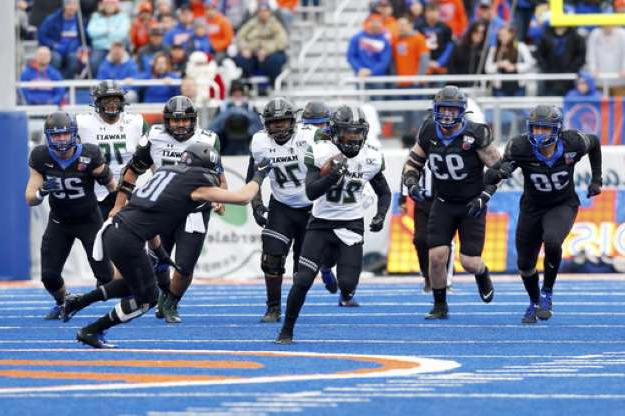 a group of people running on a track: Hawaii running back Miles Reed, center, breaks away from the Boise State defense on a 25 yard run during the first half of an NCAA college football game for the Mountain West Championship Saturday, Dec. 7, 2019, in Boise, Idaho. (AP Photo/Steve Conner)