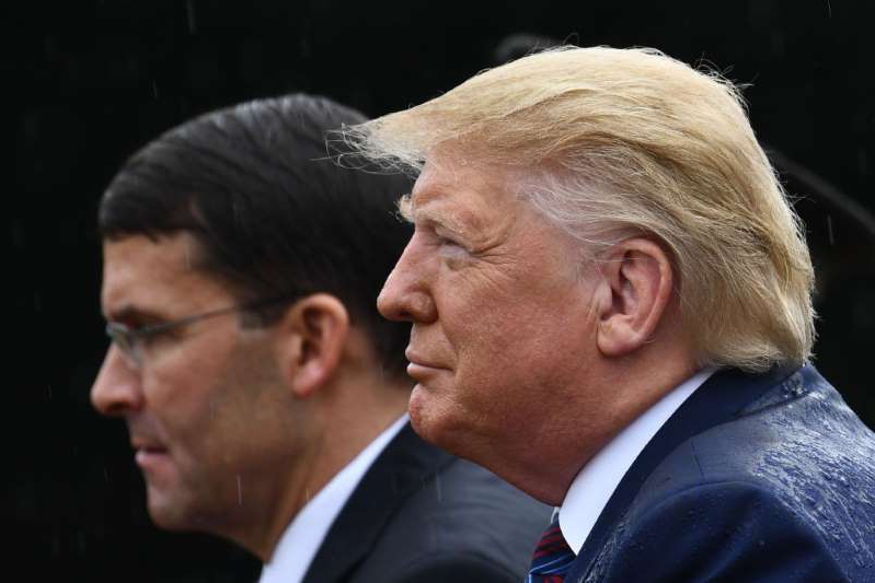 Donald Trump wearing a suit and tie: President Donald Trump and Secretary of Defense Mark Esper attend the Armed Forces Welcome Ceremony in honor of the Twentieth Chairman of the Joint Chiefs of Staff on September 30 at Summerall Field, Joint Base Myer-Henderson Hall, Virginia