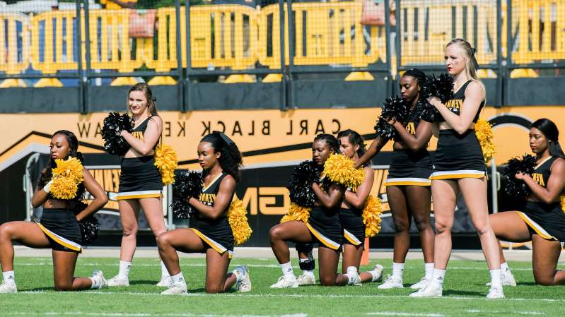 Ezinne Okwuosa et al. sitting around a football ball: Tommia Dean, front center, is one of five cheerleaders who took a knee during the national anthem at a Kennesaw State University football game in 2017.