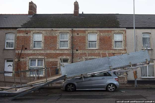a car parked in front of a brick building: A Mercedes was crushed under scaffolding that fell from the side of a house overnight on Clive Street, Cardiff, amid the severe gales