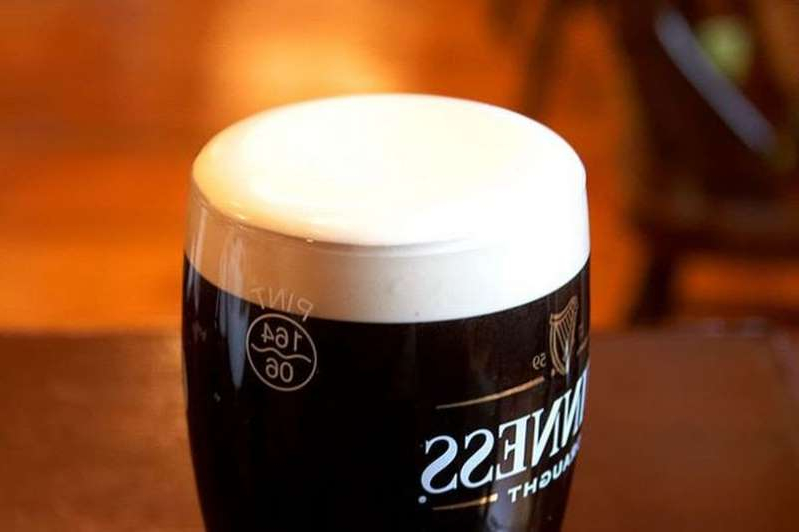 a glass of beer on a table: A pint of Guinness