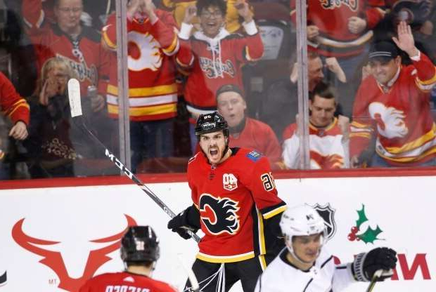 a group of people racing each other on a snow covered slope: Calgary Flames' Zac Rinaldo, top, celebrates after scoring his first goal of the season in a win over the Los Angeles Kings on Saturday.