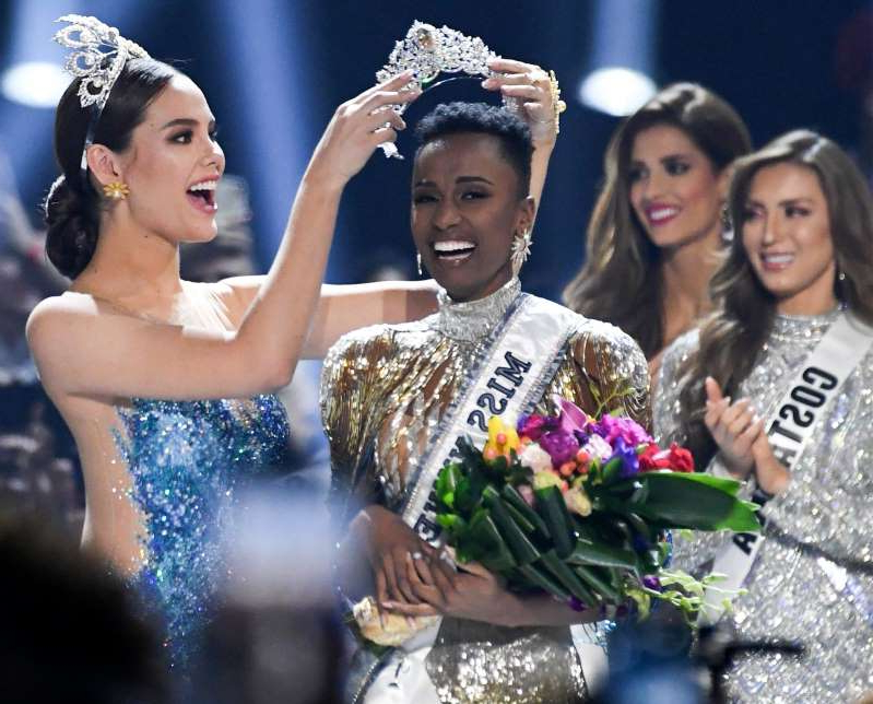 a group of people standing next to a woman: Miss South Africa Zozibini Tunzi is crowned Miss Universe 2019