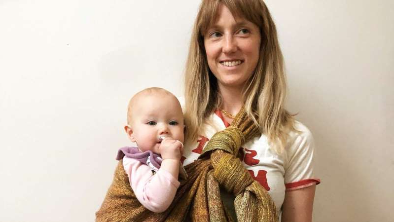 a person holding a baby: The baby wraps are sought after by customers throughout Australia and internationally. (Supplied: Pacafeathers)