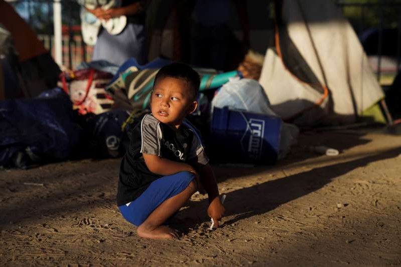 a little boy that is standing in the dirt: Honduran asylum-seeker Elias, 2, plays near the tent where he now lives in Matamoros, Mexico, on Dec. 7, 2019.