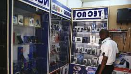 a man standing in front of a refrigerator: A man looks at smartphones on display at a shop at Wuse II business district in Abuja