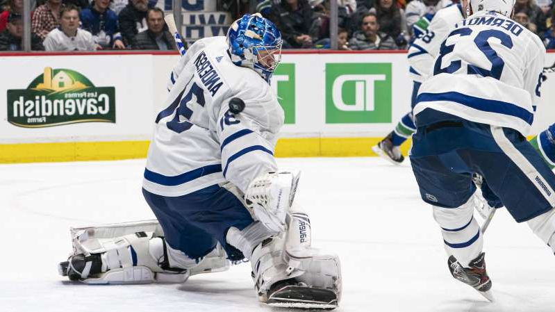 a group of hockey players on the field: VANCOUVER, BC - DECEMBER 10: Goalie Frederik Andersen #31 of the Toronto Maple Leafs makes a save against the Vancouver Canucks at Rogers Arena on December 10, 2019 in Vancouver, Canada.