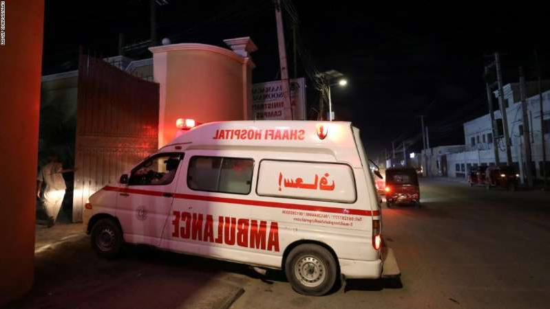 a red white and black truck sitting on top of a car: An ambulance carrying a victim from an attack by Al-Shabaab gunmen on a hotel near the presidential residence arrives at the Shaafi hospital in Mogadishu.