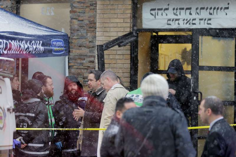 Jersey City's mayor Steven Fulop, center right, talks with first responders at the scene of a shooting in Jersey City, N.J., Wednesday, Dec. 11, 2019. Fulop says gunmen targeted a kosher market during a shooting that killed multiple people Tuesday. (AP Photo/Seth Wenig)