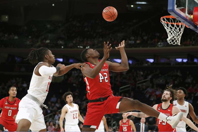 Texas Tech center Russel Tchewa (54) looks to grab the ball as Louisville forward Aidan Igiehon (22) tries to stop him during the first half of an NCAA college basketball game in the Jimmy V Classic, Tuesday, Dec. 10, 2019, in New York. (AP Photo/Kathy Willens)