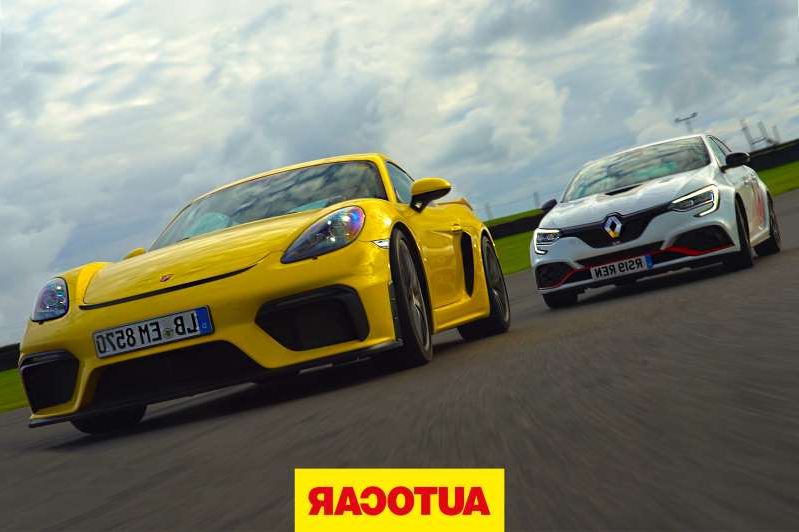 a black and yellow car in a parking lot: Porsche Cayman GT4 v Renault Megane RS Trophy R review - which is fastest?