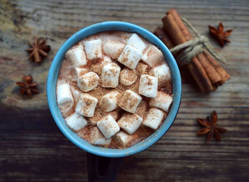 a bowl of food: hot chocolate with marshmallows and cinnamon in a blue mug