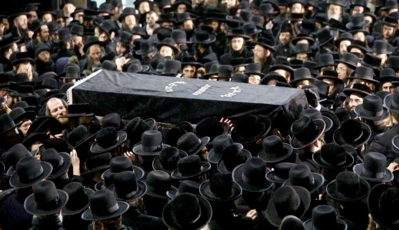 a large crowd of people: The casket of Moshe Deutch is carried to a hearse as thousands of Orthodox Jewish men crowded Rodney Street in Williamsburg, Brooklyn Wednesday night for the funeral Deutch, one of the victims of the fatal shooting in Jersey City.