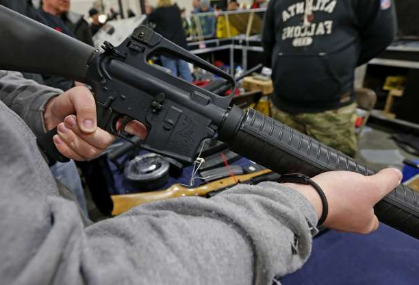 a man holding a weapon: A man holds a Bushmaster AR-15 Model A2 semi-automatic assault rifle at the Rocky Mountain Gun Show in Sandy, Utah, U.S., on Saturday, Jan. 5, 2013.