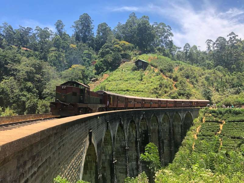 a train crossing a bridge over a river: Train through Ella, Sri Lanka.