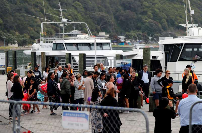 a group of people standing in front of a crowd: FILE PHOTO: Relatives wait for rescue mission, following the White Island volcano eruption in Whakatane