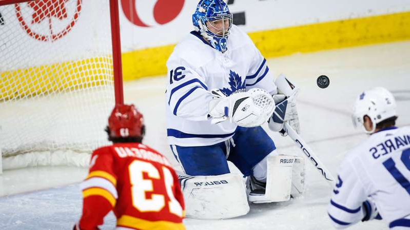 a hockey player standing in the snow: flames-leafs