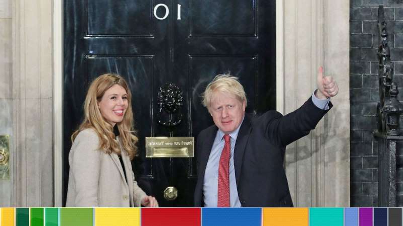 Boris Johnson standing in front of a building: Boris Johnson returns to No 10 with girlfriend Carrie Symonds after the Conservatives' emphatic victory