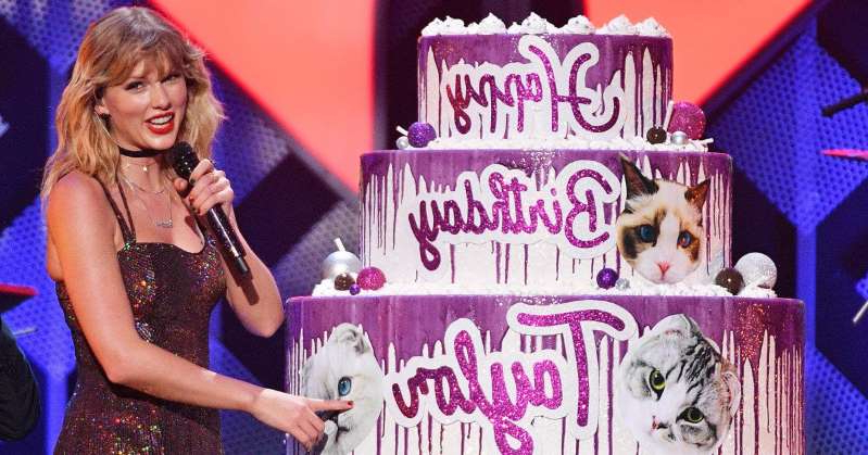 a girl posing for a picture: Taylor Swift Gets Surprised by Elvis Duran at Jingle Ball with a Massive Cake for Her Birthday