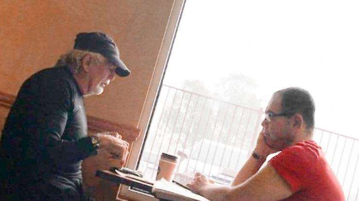 a man standing in front of a laptop: An IBAC surveillance photo of Casey councillor Sam Aziz (left) and developer John Woodman (right) at a Subway restaurant in April 2018.