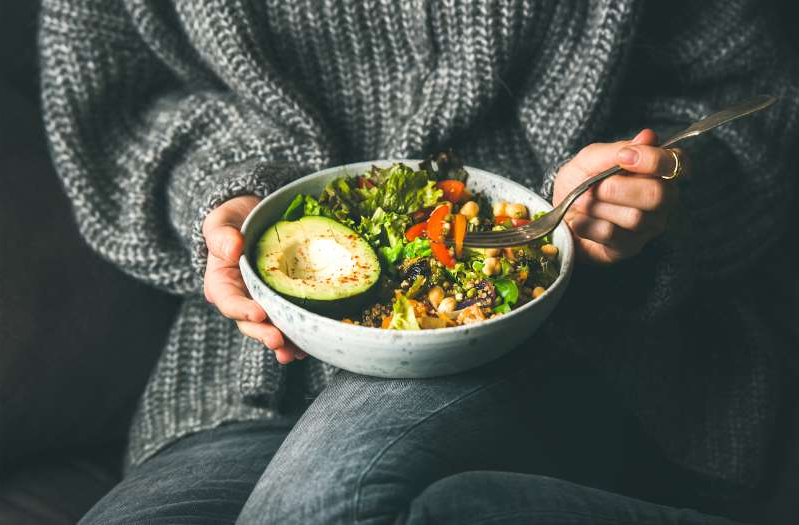 a person holding a bowl of food: plant based diet beginners mistakes