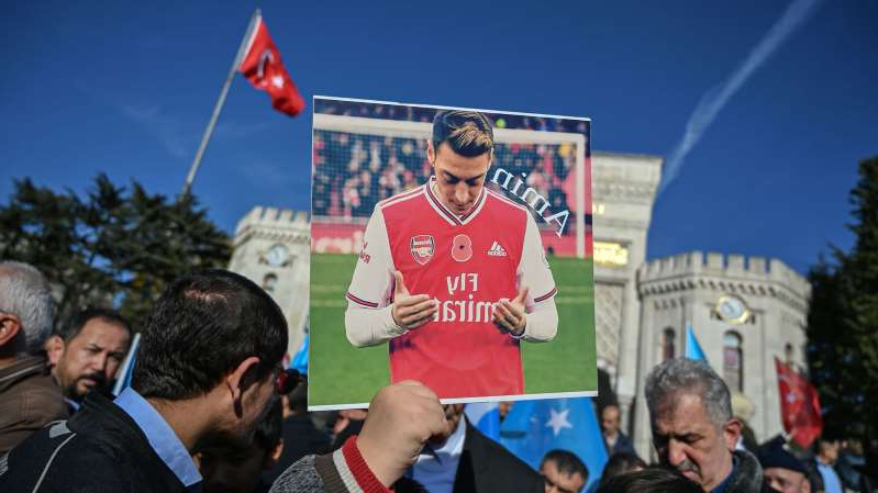 a group of people standing in front of a crowd: A supporter of China's Muslim Uighur minority holds a placard of Arsenal's Turkish origin German midfielder Mesut Ozil during a demonstration at Beyazid square in Istanbul on December 14, 2019. - Arsenal's Mesut Ozil, a German footballer of Turkish origin, expressed on December 14, 2019 support for Uighurs in Xinjiang and criticised Muslim countries for their failure to speak up for them. (Photo by Ozan KOSE / AFP) (Photo by OZAN KOSE/AFP via Getty Images)
