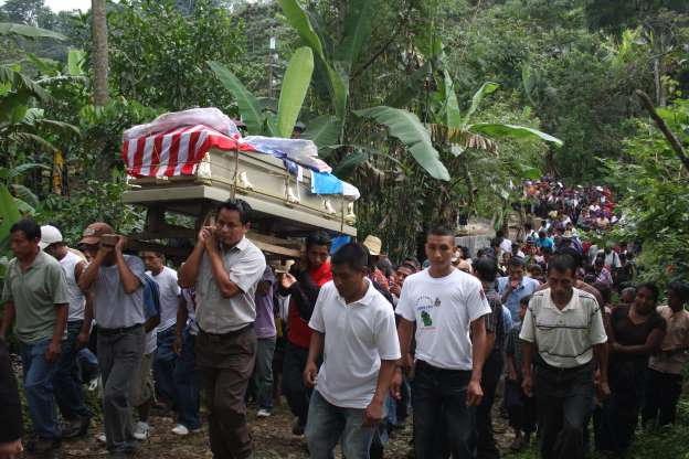 a group of people standing in front of a crowd: Caserio Xexac, Guatemala: More than 500 villagers gathered in a processsion through Xexac to carry Manuel Jaminez Xum's body to the cemetery, where he was placed inside a crypt under a giant cypress tree.