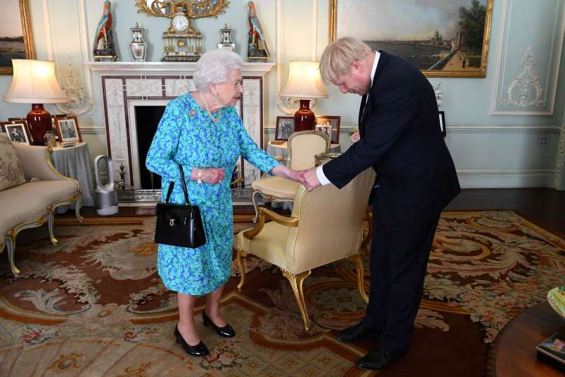 a man and a woman standing in a room: FILE PHOTO:  Boris Johnson arrives at Buckingham Palace in London for an audience with Queen Elizabeth II, in London