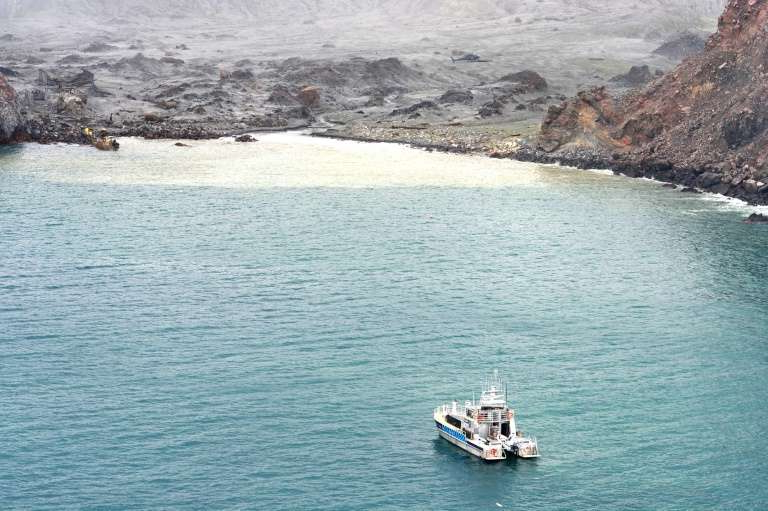 a small boat in a large body of water: Divers searching the contaminated waters around New Zealand's volcanic White Island on Saturday failed to locate one body seen floating in the area several days ago