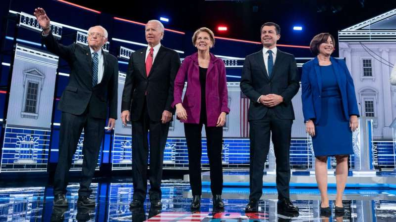 Peter Buttigieg, Elizabeth Warren, Joe Biden, Bernie Sanders posing for the camera: Sen. Amy Klobuchar, South Bend, Ind., Mayor Pete Buttigieg, Sen. Elizabeth Warren, Former vice president Joe Biden, and Sen. Bernie Sanders appear on stage at the start of he Democratic presidential debate at Tyler Perry Studios.