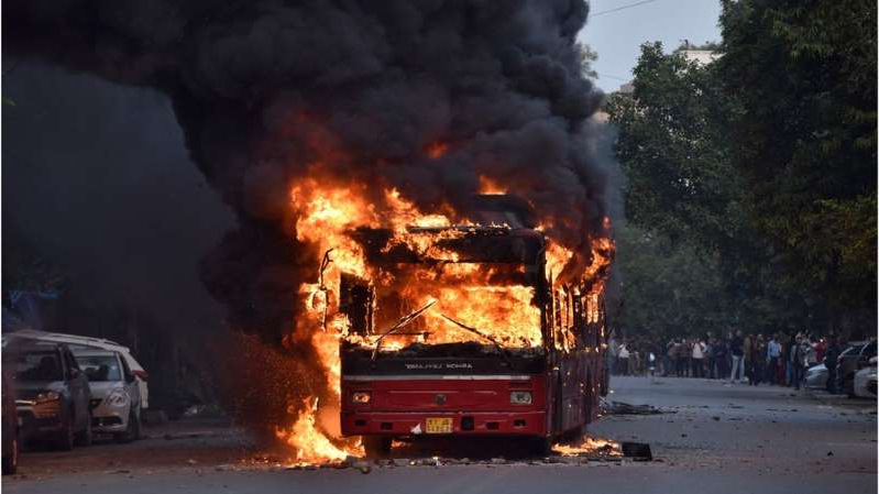a car on fire with smoke coming out of it: Buses were torched in Delhi on Sunday