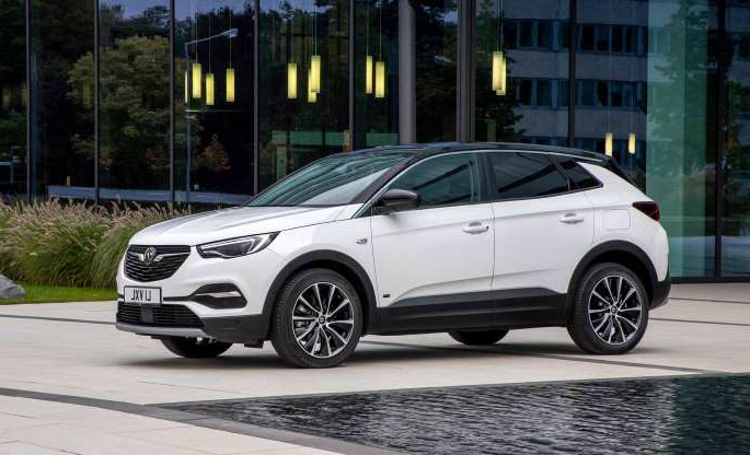 a car parked on the side of a building: Vauxhall adds front-drive Grandland X Hybrid as cheaper option