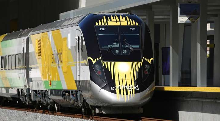 a train on a steel track: train, brightline, travel