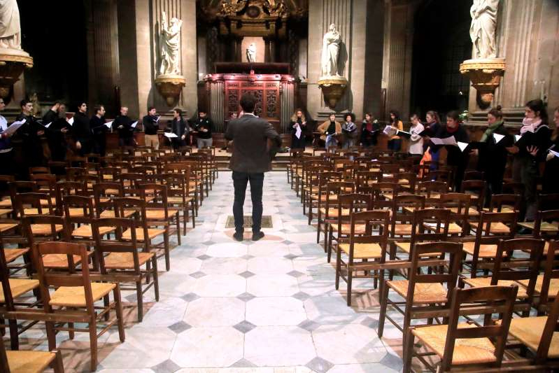 In this photo taken Monday, Dec. 16, 2019, Notre Dame cathedral choir's director Henri Chalet directs the Notre Dame choir during a rehearsal at the Saint Sulpice church in Paris. Notre Dame Cathedral kept holding services during two world wars as a beacon of hope amid bloodshed and fear. It took a fire in peacetime to finally stop Notre Dame from celebrating Christmas Mass for the first time in more than two centuries. (AP Photo/Michel Euler)
