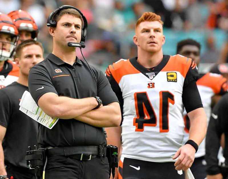 Andy Dalton et al. standing in front of a crowd: Cincinnati Bengals head coach Zac Taylor (right) stands next to Bengals quarterback Andy Dalton (left) on the sidelines during the first half against the Miami Dolphins at Hard Rock Stadium.