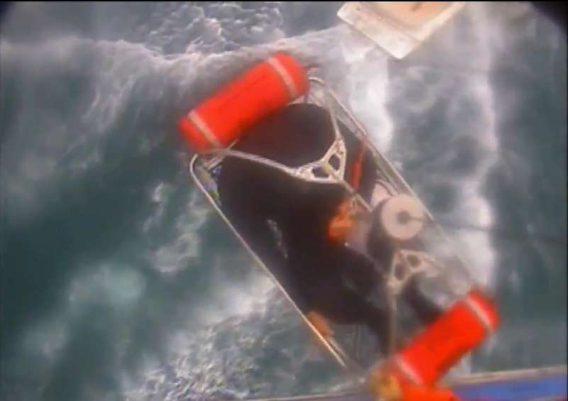 In this Saturday, Dec. 21, 2019, video image released by the U.S. Coast Guard shows a man, wearing a full-body wetsuit, being hoisted up from the boat into the helicopter near Santa Rosa Island, one of the Channel Islands in Southern California. A shark reportedly bit a surfer Saturday afternoon in a