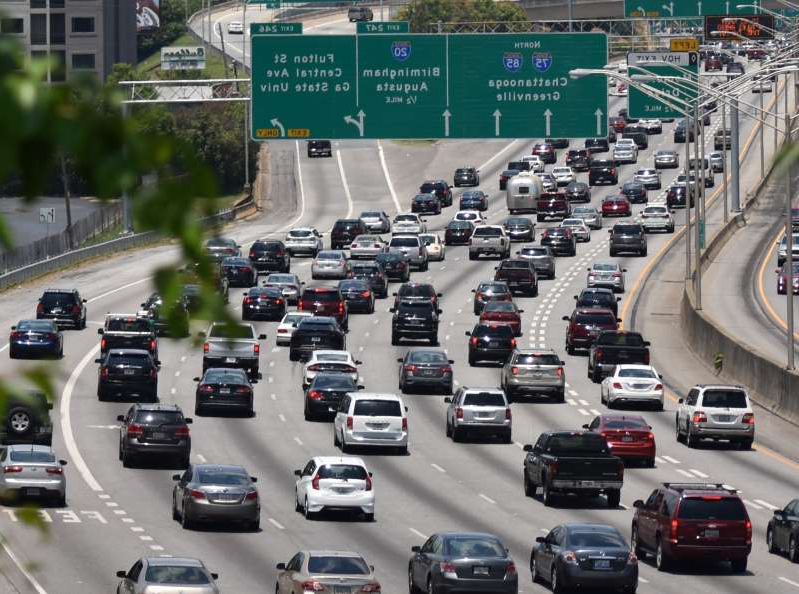 a car driving down a busy street filled with traffic next to a highway: Atlanta interstate traffic headed North toward Downtown. Image: Getty