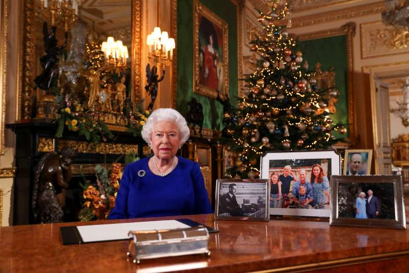 Elizabeth II sitting at a table in front of a building: Britain's Queen Elizabeth poses, after recording her annual Christmas Day message in Windsor Castle, in Berkshire