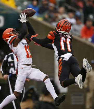 a group of baseball players standing on top of a field: Cleveland Browns cornerback Denzel Ward (21) catches an interception against Cincinnati Bengals wide receiver John Ross (11) during the second half of an NFL football game, Sunday, Dec. 29, 2019, in Cincinnati. (AP Photo/Gary Landers)