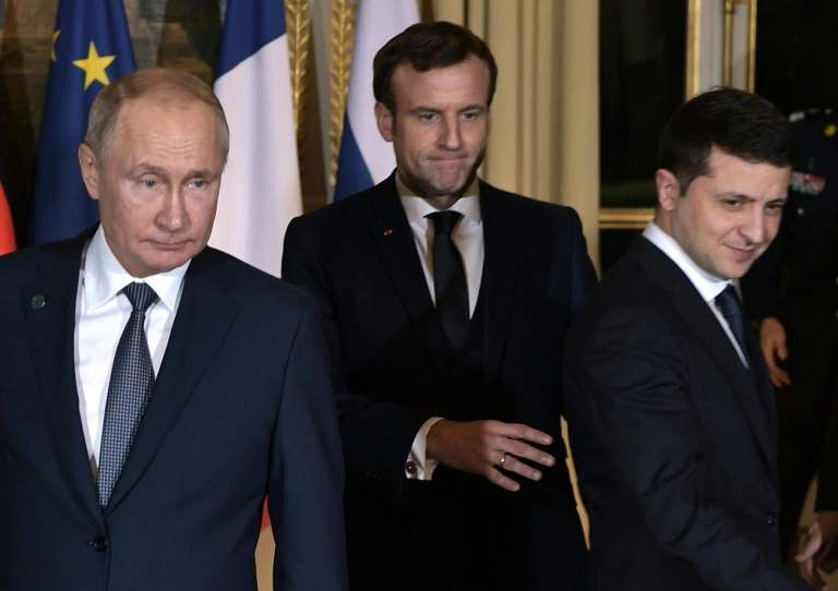 Emmanuel Macron, Vladimir Putin standing next to a man in a suit and tie: The swap came after a meeting between the Russian and Ukrainian leaders in Paris this month
