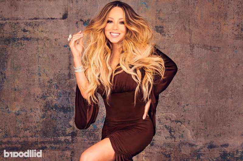 Mariah Carey standing in front of a brick wall