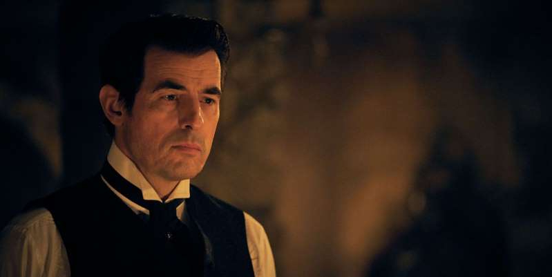 Claes Bang wearing a suit and tie looking at the camera: BBC's Dracula has revealed a major connection to the Doctor Who universe with a reference to Clara Oswald.